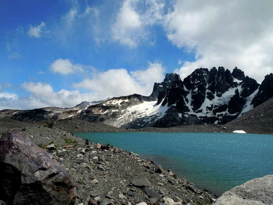 A turquoise lake at the top of Cerro Castillo in Northern Patagonia rests beneath the basalt spires of the mountain. Photo: Brian Chasnoff, San Antonio Express-News / © 2014 San Antonio Express-News