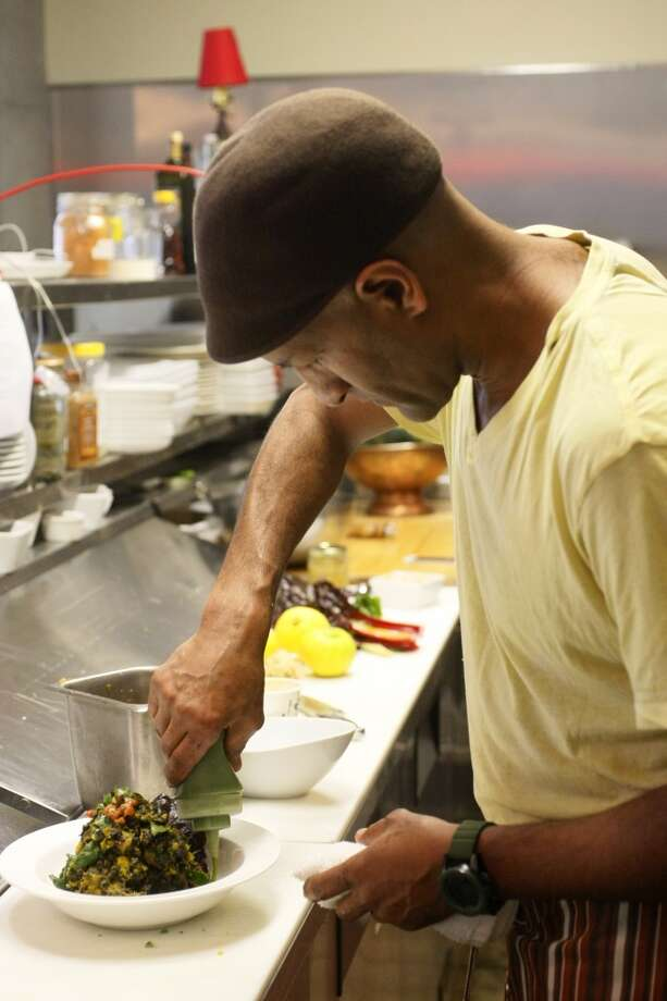 Chef Eskender Aseged puts sauce on kabocha squash alicha at his restaurant at Radio Africa & Kitchen. Photo: Codi Mills, The Chronicle
