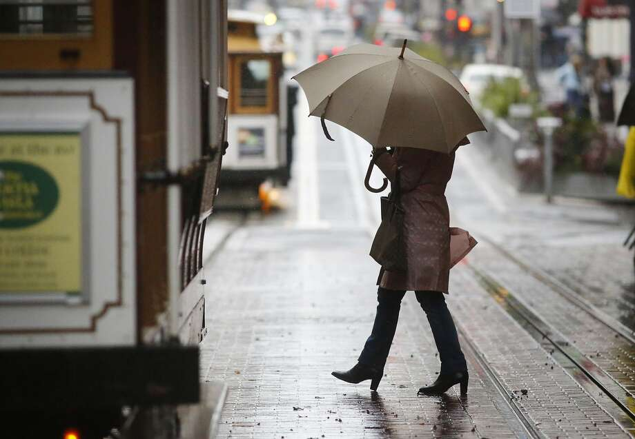 Lucy Lima, visiting San Francisco from Natal, Brazil, heads toward a Powell Street cable car as a major storm hits the city. Photo: Mike Kepka, The Chronicle