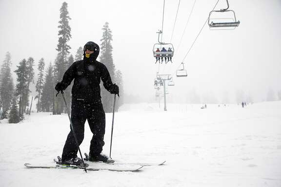 Kirk Anderson of Ripon, CA stands under a ski lift as he waits for friends at the bottom of a run at Sierra at Tahoe ski resort in South Lake Tahoe, CA, Saturday March 29, 2014.