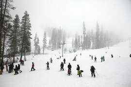 Skiers and snowboarders make their way down a run as snow falls during a late season storm at Sierra at Tahoe ski resort in South Lake Tahoe, CA, Saturday March 29, 2014.