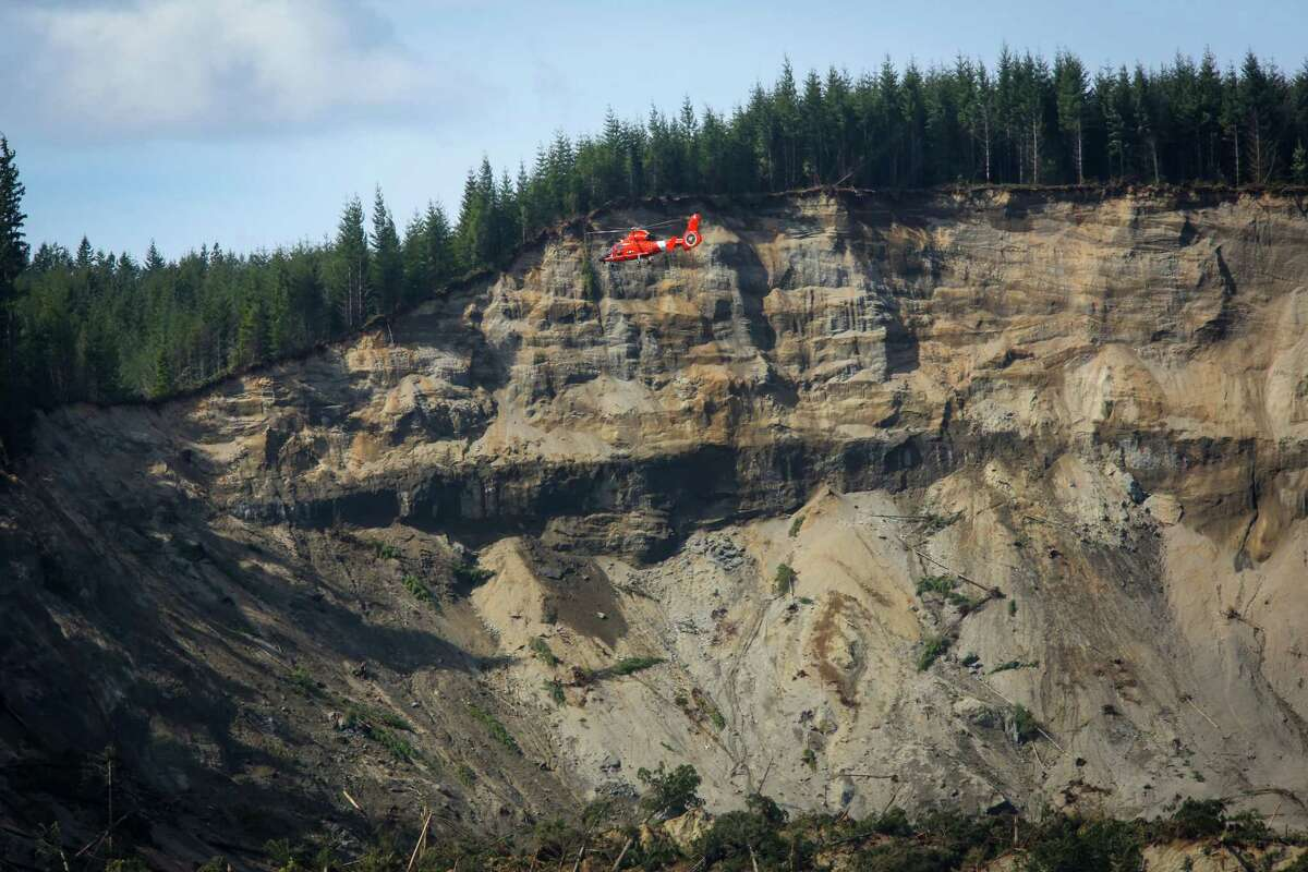 A U.S Coast Guard helicopter flies over the site of the Oso mudslide on Monday, March 31, 2014 near Darrington. Work continues in the debris field as workers try to account for victims of the disaster.