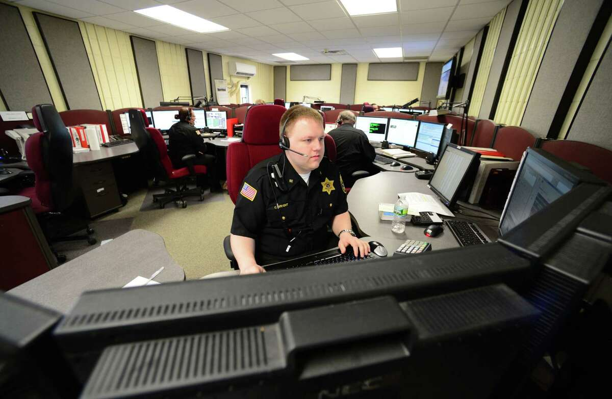 Desk officer Chris Wright of the Saratoga County Sheriff's Office works 911 calls at Saratoga County's dispatch center Monday morning, March 31, 2014, in Ballston Spa, N.Y. Saratoga County's ability to handle 911 calls was limited Sunday and Monday because half of the phone lines were down. Verizon was on the scene making repairs Monday morning. (Will Waldron/Times Union)