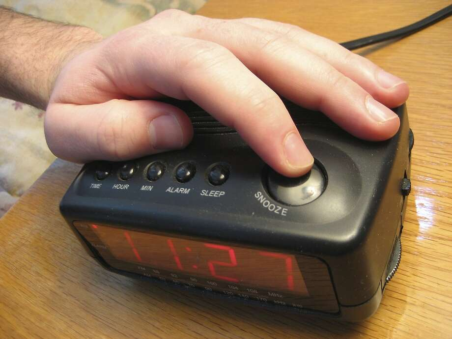 Hand reaching to press the snooze button on an alarm clock Photo: Istockphoto