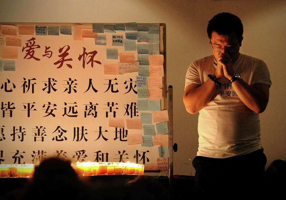 A Chinese man prays for relatives who were on Malaysia Airlines Flight 370 before a meeting in a Beijing hotel. Photo: Wang Zhao / Getty Images / AFP