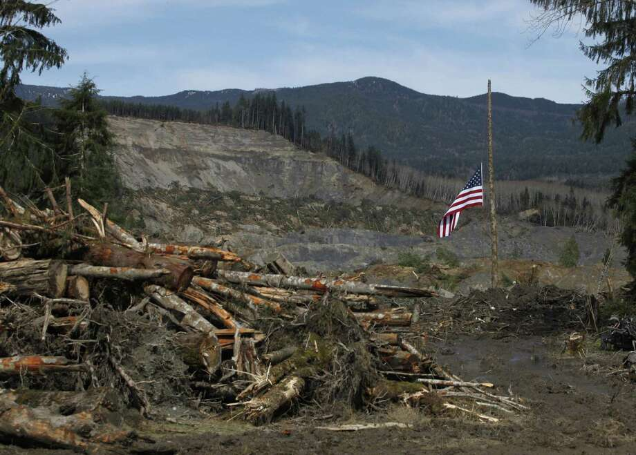 An American flag hangs from the only cedar post left standing at the scene of the mudslide in Oso, Wash. Gov. Jay Inslee is asking the federal government for a major disaster declaration. Photo: Sofia Jaramillo / Associated Press / Pool, The Herald