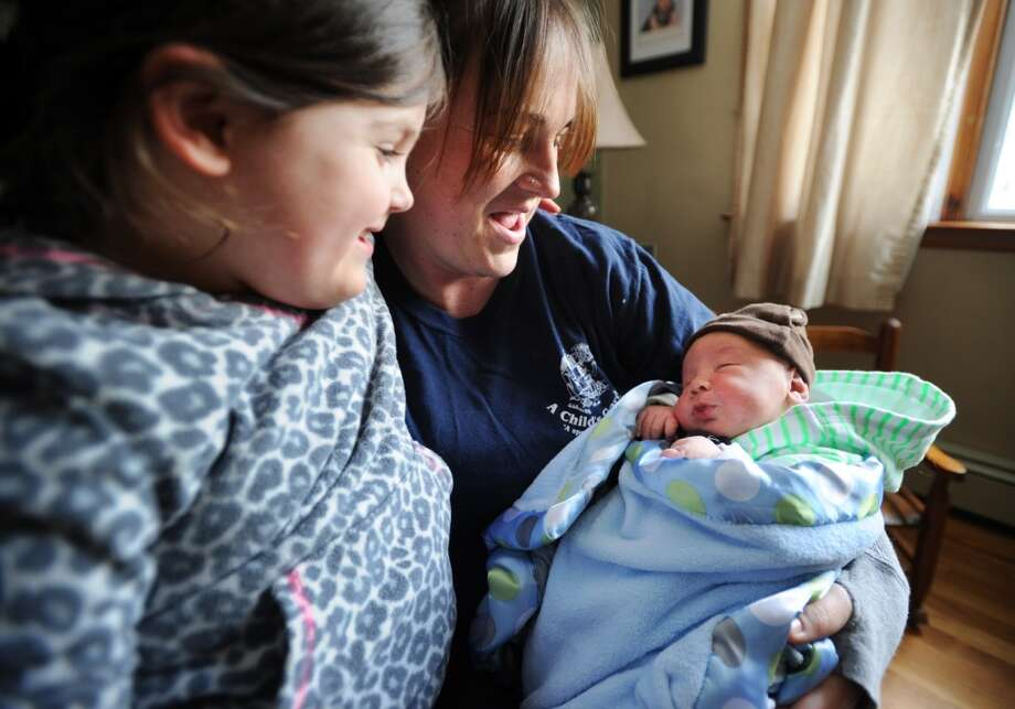 Jennifer Scollin and daughter Kelsey Dillman, 4, with newborn Cole Dillman at their Tracy Terrace home in Seymour, Conn. on Monday, March 31, 2014. Scollin, who says she didn't know she was pregnant, gave birth to the nine pound Cole in an ambulance in her driveway on Saturday morning. Photo: Brian A. Pounds