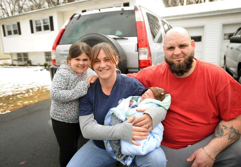 Jennifer Scollin and Matthew Dillman with their children Kelsey Dillman, 4, and newborn Cole Dillman outside their Tracy Terrace home in Seymour, Conn. on Monday, March 31, 2014. Scollin, who says she didn't know she was pregnant, gave birth to the nine pound Cole in an ambulance in her driveway on Saturday morning. Photo: Brian A. Pounds