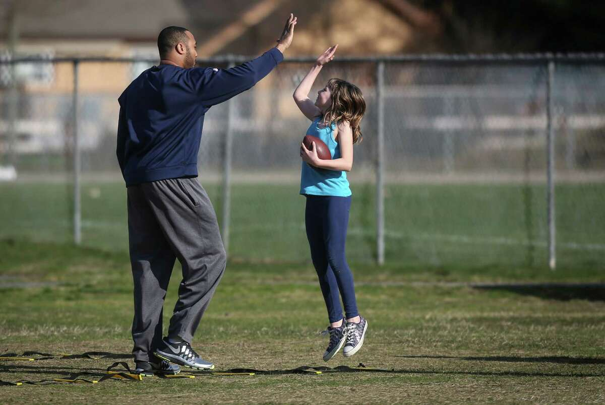 Seattle Seahawks player K.J. Wright gets a high-five as Seahawks and Sounders players hold a football camp with local residents on Monday, March 31, 2014 in Darrington. Players and team officials from the Sounders and Seahawks visited Darrington to lend support to locals after the deadly mudslide that hit nearby Oso.