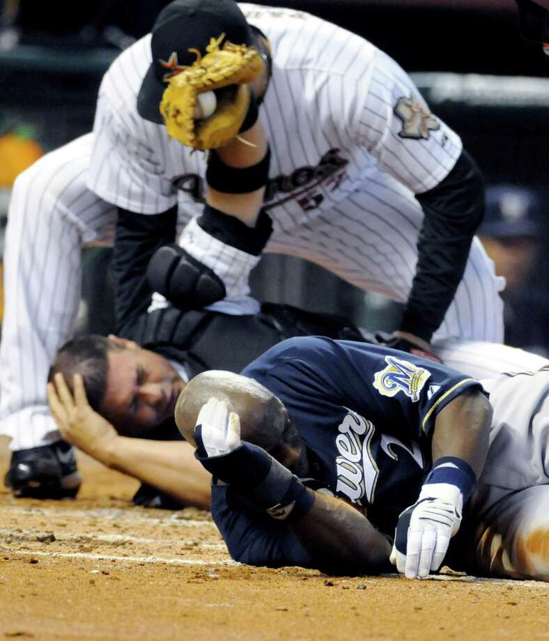 Milwaukee Brewers' Mike Cameron, right, and Houston Astros catcher Humberto Quintero hold their heads after colliding at home plate in the fourth inning in a baseball game Friday, April 24, 2009 in Houston. Cameron was out on the play and Quintero left the game. (AP Photo/Pat Sullivan) Photo: Pat Sullivan, STF / AP