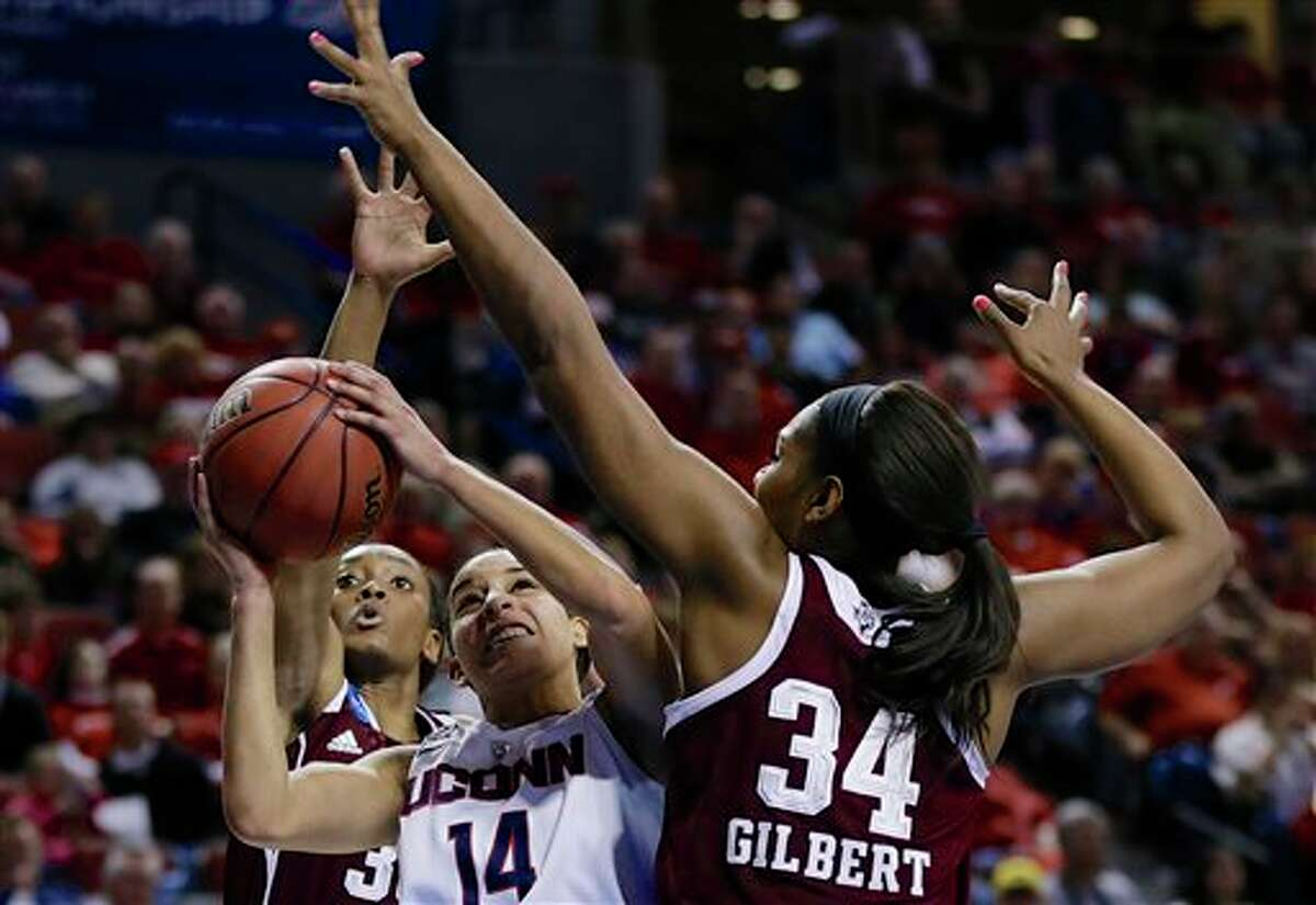 Connecticut's Bria Hartley (14) shoots against the defense of Texas A&M's Courtney Walker, rear, and Texas A&M's Karla Gilbert (34) during the first half of a regional final game in the NCAA college basketball tournament in Lincoln, Neb., Monday, March 31, 2014. (AP Photo/Nati Harnik)