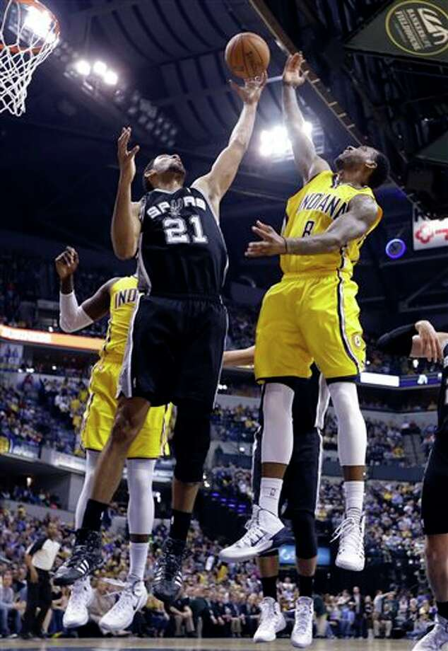 San Antonio Spurs forward Tim Duncan (21) grabs a rebound in front of Indiana Pacers guard Rasual Butler in the first half of an NBA basketball game in Indianapolis, Monday, March 31, 2014.  (AP Photo/Michael Conroy) Photo: Michael Conroy, AP / AP
