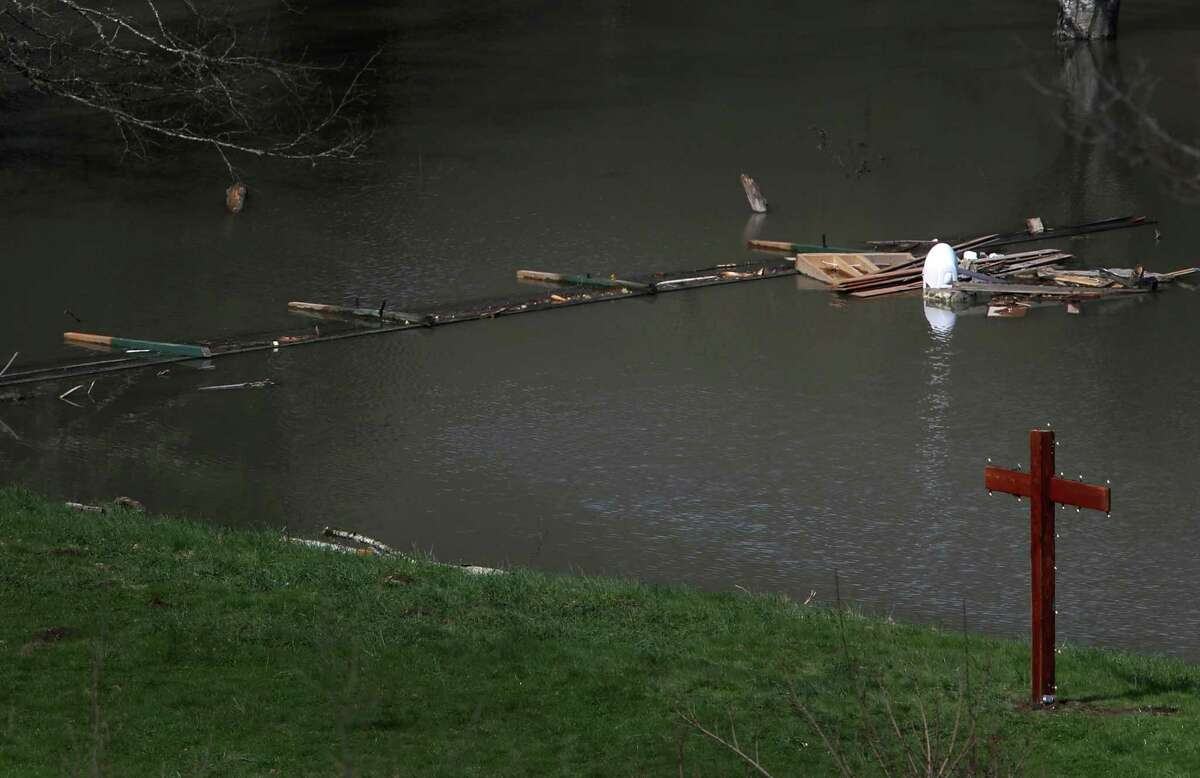 A newly-erected cross is shown at the edge of the flooded Stillaguamish River on the property of Don and Elaine Young near Oso on Monday, March 31, 2014. Work continues in the debris field of the Oso mudslide that left dozens dead.