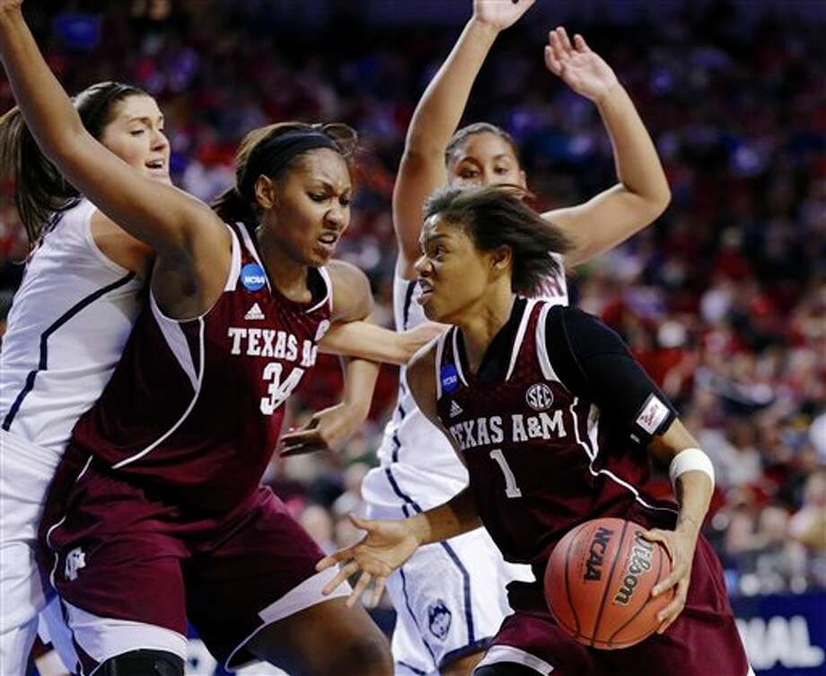 Texas A&M's Courtney  Williams (1) drives to the basket past teammate Karla Gilbert (34),  Connecticut's Stefanie Dolson, left, and Connecticut's Kaleena  Mosqueda-Lewis, right rear, during the second half of a regional final  game in the NCAA college basketball tournament in Lincoln, Neb., Monday,  March 31, 2014. (AP Photo/Nati Harnik)