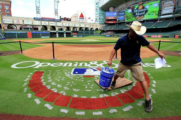 Minute Maid Park grounds crew member,  James Vaughn, works on painting the Opening Series logo behind home plate, Monday, March 31, 2014, in Houston. Houston Astros opening day is Tuesday. ( Karen Warren / Houston Chronicle  )