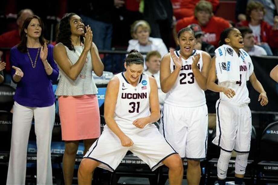 Connecticut's Stefanie Dolson  (31) does a victory dance as teammates Kaleena Mosqueda-Lewis (23) and  Moriah Jefferson (4) celebrate their win of a regional final game in the  NCAA college basketball tournament in Lincoln, Neb., Monday, March 31,  2014.  Connectiut defeated Texas A&M 69-54. (AP Photo/The Omaha  World-Herald/Matt Miller)