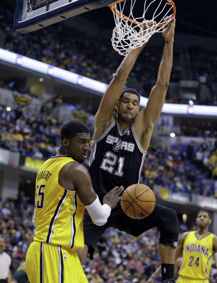 Tim Duncan of the Spurs throws down a dunk in the face of Pacers center Roy Hibbert in the second half. The veteran power forward contributed nine points, six rebounds and four assists in nearly 31 minutes of play. Photo: Michael Conroy / Associated Press / AP