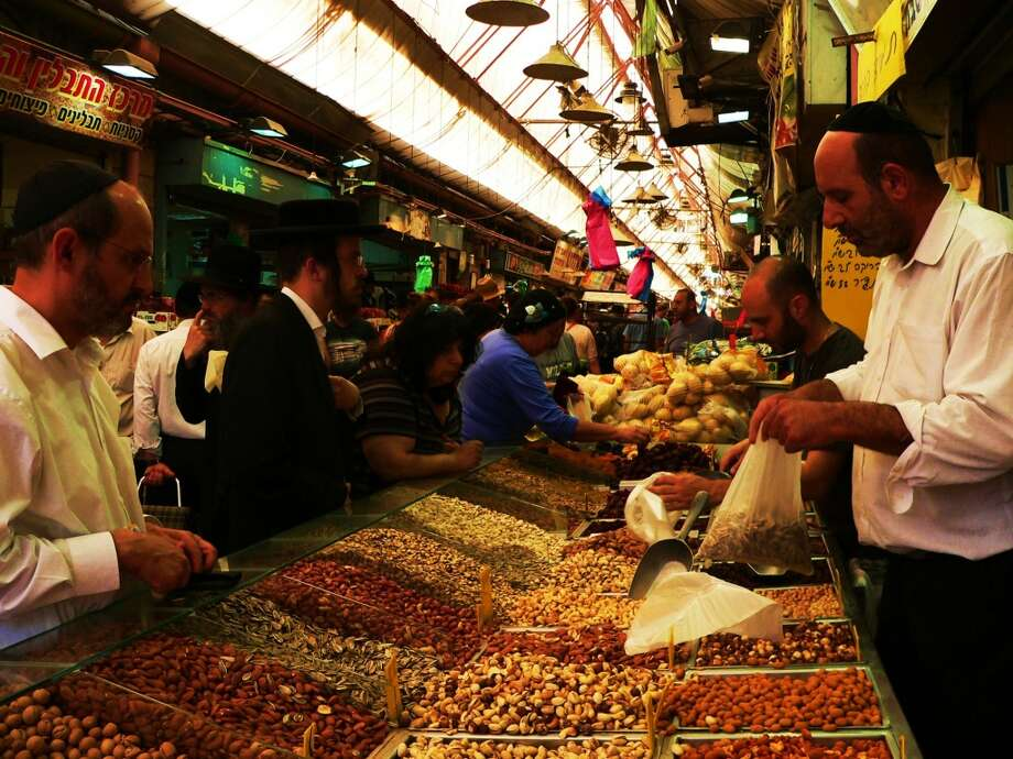 Shoppers of all types shop for foodstuffs at Jerusalem''s outdoor Machneyuda market. Photo: By Wendy Lemlin, For The Express-News