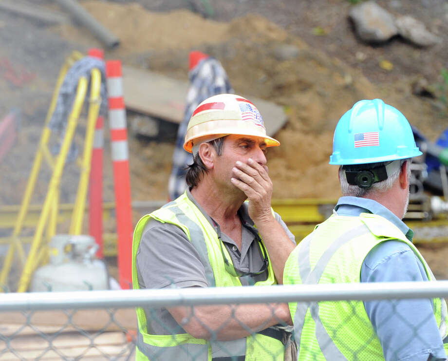 A worker puts his hand to his face at the site of a power failure near the Mount Vernon East, N.Y., train station, Friday, Sept. 27, 2013. A damaged high-voltage feeder cable has affected Metro-North rail service on the New Haven Line. Photo: Bob Luckey / Greenwich Time