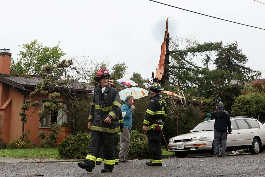 Neighbors and firefighters stop to look at what's left of a redwood tree that was recently struck by lightning in Berkeley , Calif. on March 31, 2014. The tree splintered into thousands of pieces, of various sizes around the neighborhood. Photo: Deborah Svoboda, The Chronicle