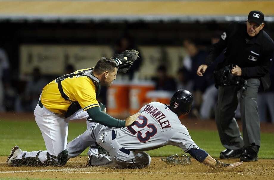 The Indians' Michael Brantley is tagged out in the sixth by A's catcher John Jaso, a call that was reviewed via replay and upheld. Photo: Carlos Avila Gonzalez, The Chronicle