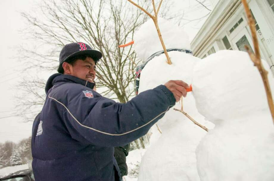 Nulfo De La Cruz puts the finishing touches on a snowman during a snowstorm in Stamford, Conn. on Tuesday, Feb. 10, 2010. Photo: Chris Preovolos / Stamford Advocate