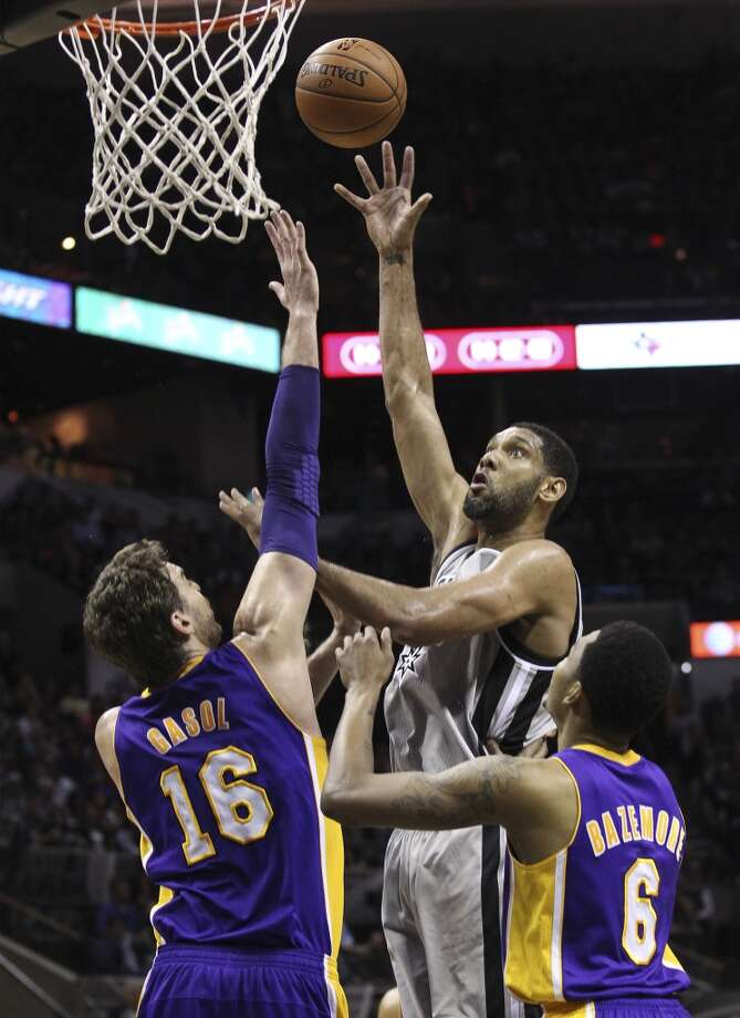 Spurs' Tim Duncan (21) takes a shot against Los Angeles Lakers' Pau Gasol (16) and Kent Bazemore (06) in the first half at the AT&T Center on Friday, March 14, 2014. Photo: Kin Man Hui, San Antonio Express-News