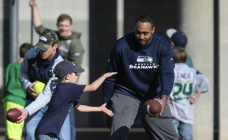 Seattle Seahawks player K.J. Wright hands off the ball to a youngster as Seahawks player hold a football camp with local residents on Monday in Darrington. Photo: JOSHUA TRUJILLO, SEATTLEPI.COM / SEATTLEPI.COM