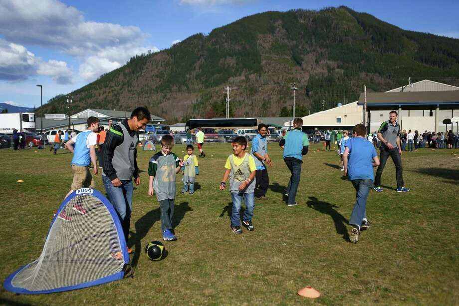 Seattle Sounders player Gonzalo Pineda, left, plays soccer with local residents. Photo: JOSHUA TRUJILLO, SEATTLEPI.COM / SEATTLEPI.COM