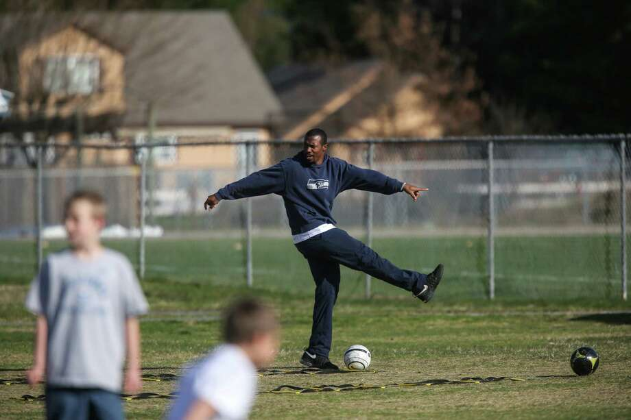 Seattle Seahawks player Chandler Fenner shows how to do a drill during a football camp for local residents  in Darrington. Players and team officials from the Sounders and Seahawks visited Darrington to lend support after the deadly mudslide that hit nearby Oso. Photo: JOSHUA TRUJILLO, SEATTLEPI.COM / SEATTLEPI.COM