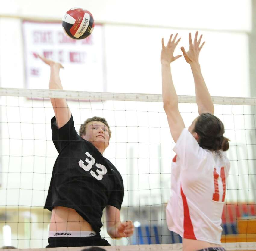 At left, New Canaan's Sean McCloskey (# 33) goes for a spike as Dexter Frisch of Greenwich (# 11) rises to meet the ball during the boys volleyball match between Greenwich High School and New Canaan High School at Greenwich, Wednesday, May 8, 2013.