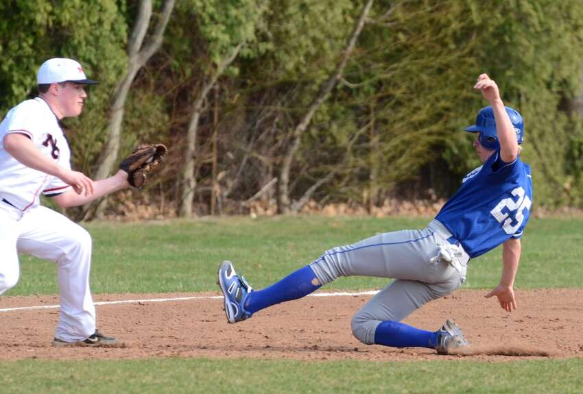 New Canaan's Alex Farina gets ready to tag Darien's Sam Gillispie at third during the baseball game at Mead Park in New Canaan on Monday, Apr. 11, 2011.