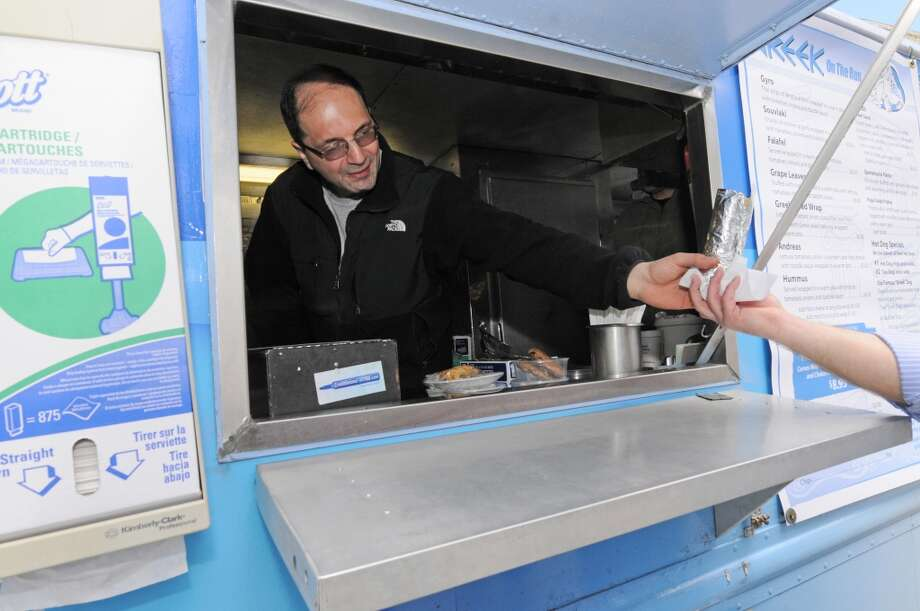 Nick Efstathiou, owner of Greek on the Run food truck, hands over an order to a customer on his first day of the year for vending outside the Capitol Monday, March 31, 2014, in Albany, N.Y.  (Paul Buckowski / Times Union) Photo: Paul Buckowski, Albany Times Union