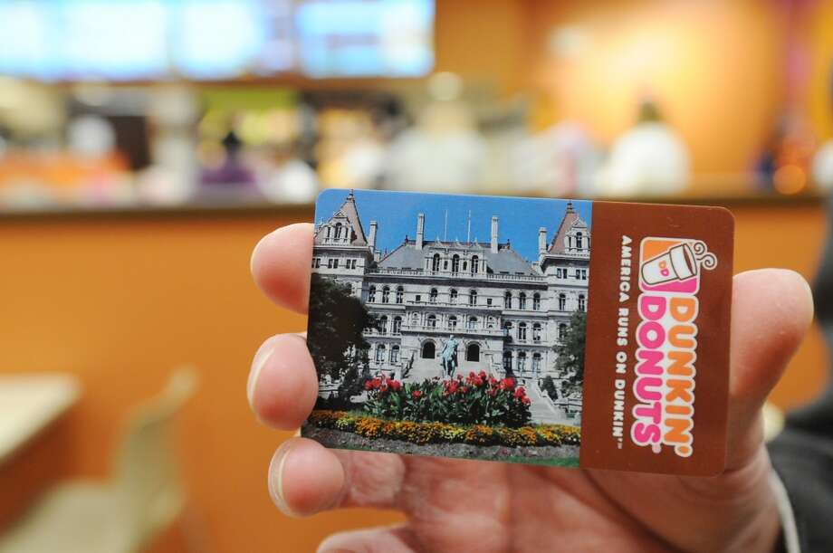 A Dunkin Donuts coffee card is displayed at the newly opened Dunkin Donuts on the first floor of the Capitol on Monday, March 31, 2014, in Albany, N.Y. On Tuesday morning at 7am, the first 500 guests through the doors will receive this specially printed, $2 Dunkin Donuts rechargeable coffee card, featuring a photo of the Capitol building. The Dunkin Donuts will be open Monday through Friday, from 7am until 6pm.  (Paul Buckowski / Times Union) Photo: Paul Buckowski, Albany Times Union