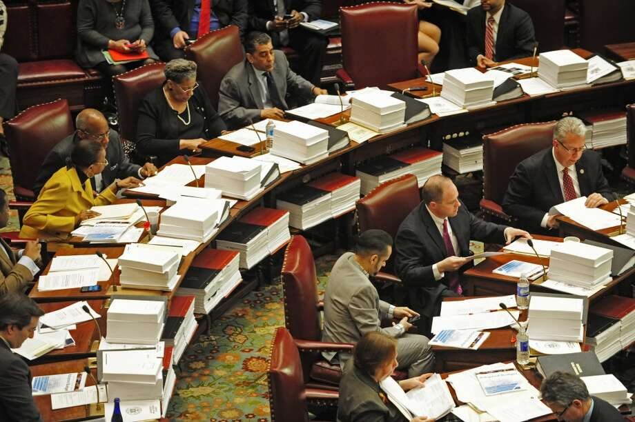 Members of the Senate read through budget bills as debate on the bills takes place on Monday, March 31, 2014, at the Capitol in Albany, N.Y.  (Paul Buckowski / Times Union) Photo: Paul Buckowski, Albany Times Union