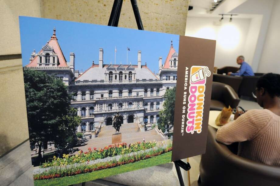 An enlarged photo of a special Dunkin Donuts coffee card is displayed at the newly opened Dunkin Donuts on the first floor of the Capitol on Monday, March 31, 2014, in Albany, N.Y. On Tuesday morning at 7am, the first 500 guests through the doors will receive this specially printed, $2 Dunkin Donuts rechargeable coffee card, featuring a photo of the Capitol building. The Dunkin Donuts will be open Monday through Friday, from 7am until 6pm.  (Paul Buckowski / Times Union) Photo: Paul Buckowski, Albany Times Union