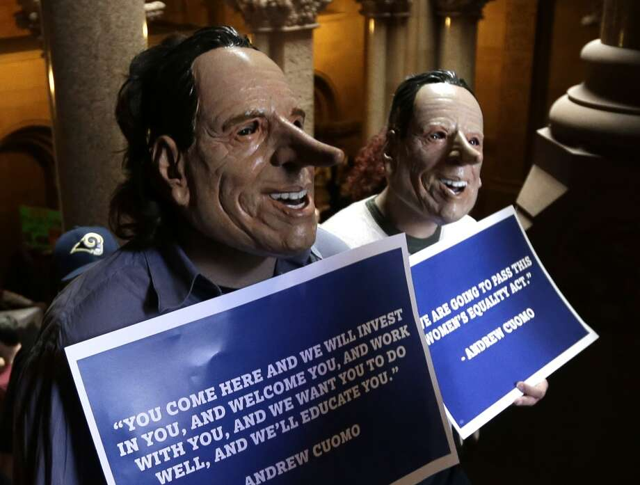 Demonstrators wearing masks resembling  Gov. Andrew Cuomo rally against the proposed state budget outside at the Capitol on Monday, March 31, 2014, in Albany, N.Y. The state Legislature began debating a $140 billion budget due by the beginning of the fiscal year at midnight. (AP Photo/Mike Groll) Photo: Mike Groll, AP
