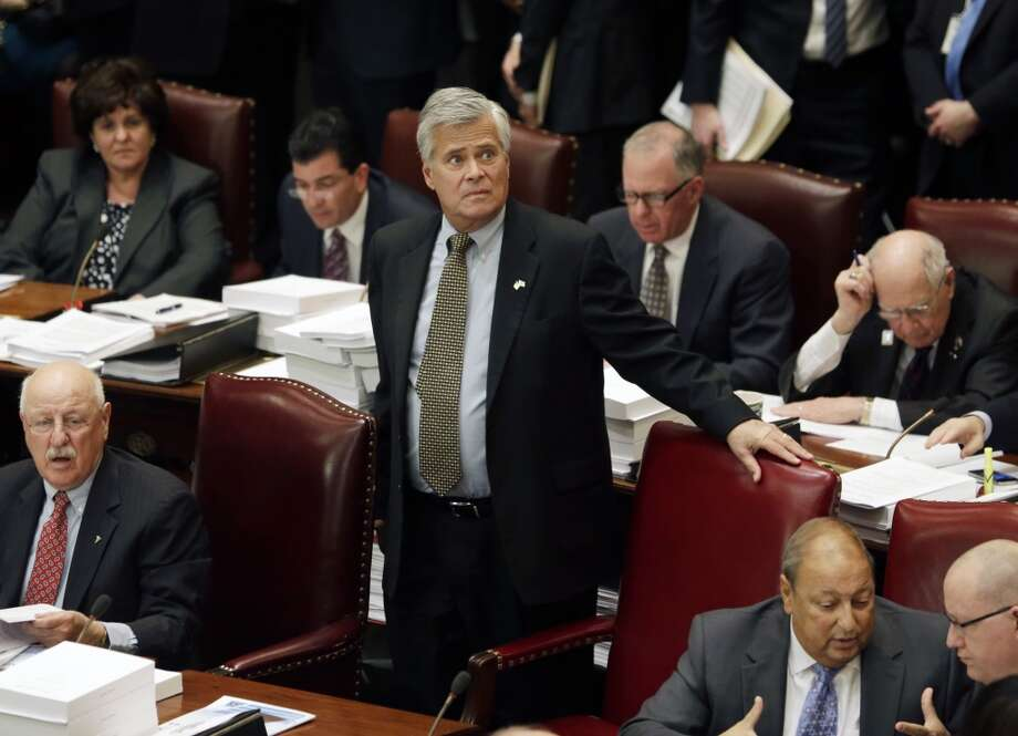 Senate Republican leader Dean Skelos, R-Rockville Centre, stands at his desk in the Senate Chamber at the Capitol on Monday, March 31, 2014, in Albany, N.Y. The state Legislature began debating a $140 billion budget due by the beginning of the fiscal year at midnight. (AP Photo/Mike Groll) Photo: Mike Groll, AP
