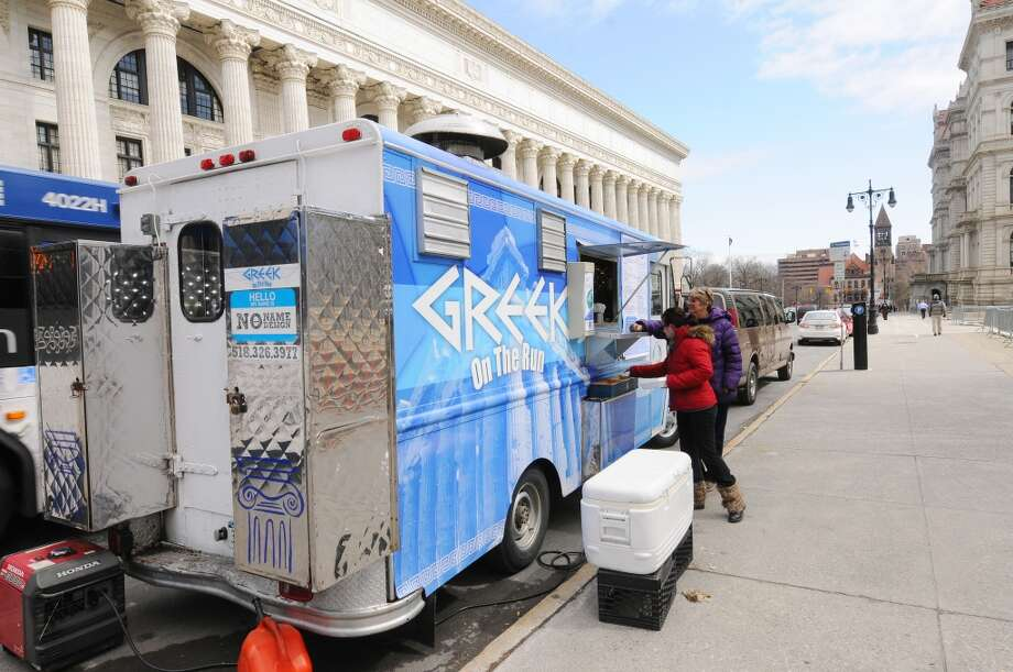 Customers get their food orders at the Greek on the Run food truck outside the Capitol on Monday, March 31, 2014, in Albany, N.Y.  Monday marked the first official vending day of the year outside the Capitol for owner Nick Efstathiou others. (Paul Buckowski / Times Union) Photo: Paul Buckowski, Albany Times Union