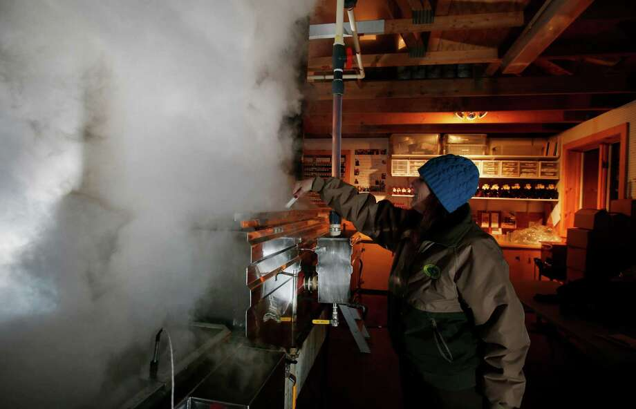 In this March 13, 2014 photo, Kathy Gallagher makes sure sap doesn't boil over   in the evaporator at the Turtle Lane Maple sugar house in North Andover, Mass. It takes about 40 gallons of sap to yield one gallon of syrup. Maple syrup season is finally under way in Massachusetts after getting off to a slow start because of unusually cold weather. (AP Photo/Elise Amendola) ORG XMIT: MAEA108 Photo: Elise Amendola, AP / AP