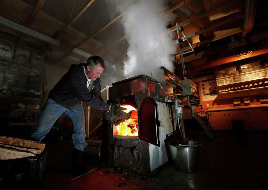 In this March 13, 2014 photo, Paul Boulanger tosses wood in to fire up the sap evaporator at the Turtle Lane Maple sugar house in North Andover, Mass. It takes about 40 gallons of sap to yield one gallon of syrup. Maple syrup season is finally under way in Massachusetts after getting off to a slow start because of unusually cold weather. (AP Photo/Elise Amendola) ORG XMIT: MAEA106 Photo: Elise Amendola, AP / AP