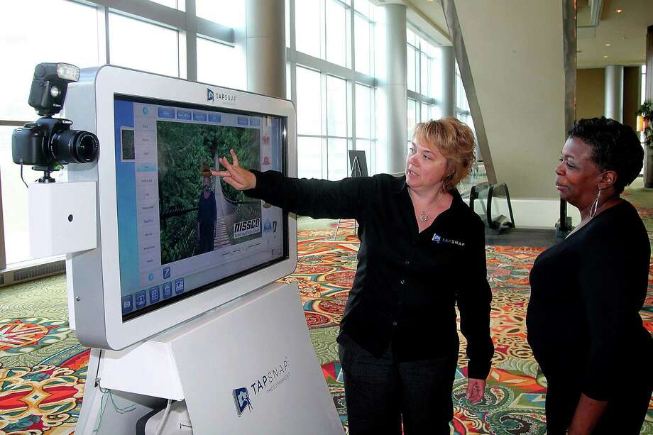 "The Woodlands-area resident Jana Witt demonstrates how to use the TapSnap photo booth to Paula Macklin. Witt calls the photo kiosk ""photoentertainment."" Photo: Pin Lim, Freelance / Copyright Pin Lim."