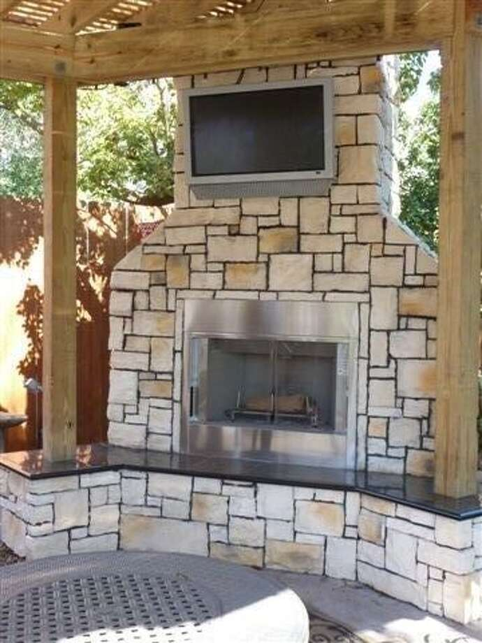 One of the newer additions to the Droeges' garden is a large stone fireplace at the side of the covered outdoor kitchen. Photo: Alvin Area Garden Tour