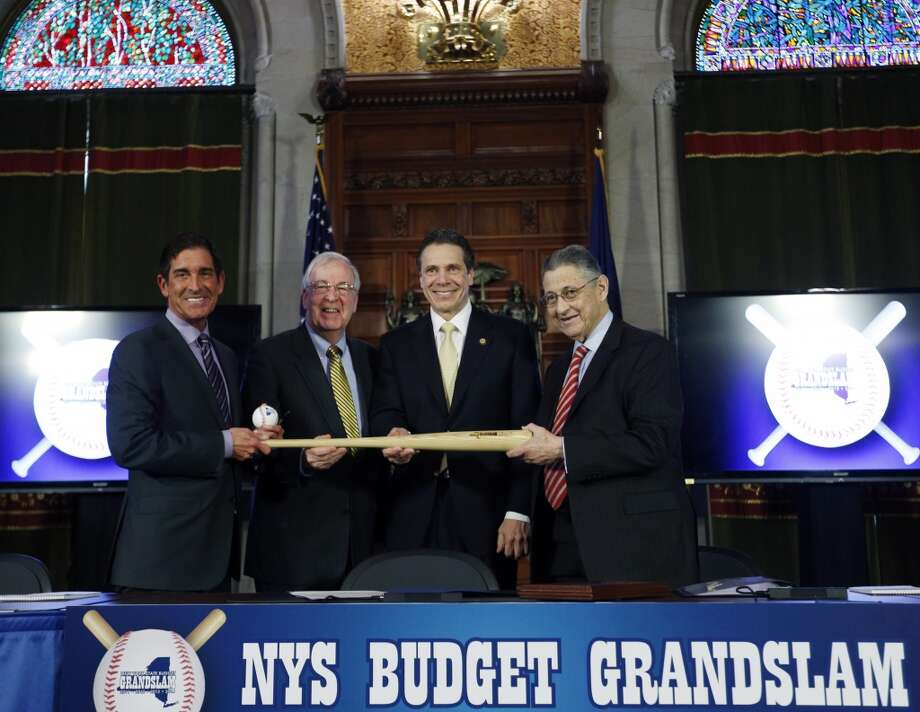 New York Gov. Andrew Cuomo, second from right, joined by, from left, Senate co-leader Jeff Klein, D-Bronx, Sen. Kemp Hannon, R-Garden City, and Assembly Speaker Sheldon Silver, D-Manhattan, pose with baseballs and a bat during a news conference and budget bill signing ceremony in the Red Room at the Capitol on Tuesday, April 1, 2014, in Albany, N.Y. The baseballs and bat represent a grand slam budget after four consecutive on-time budgets. (AP Photo/Mike Groll) Photo: Mike Groll, AP