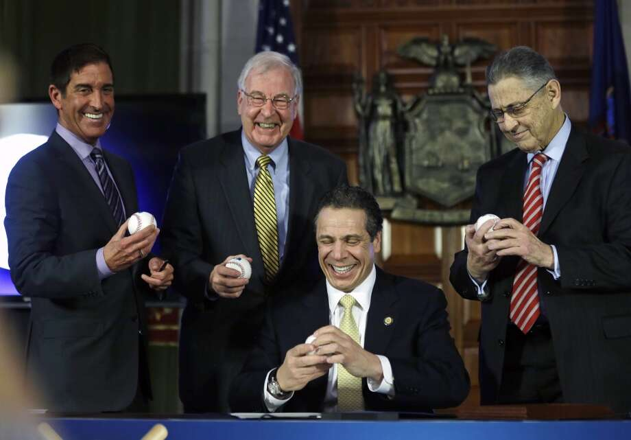 New York Gov. Andrew Cuomo, seated, Senate co-leader Jeff Klein, D-Bronx, left, Sen. Kemp Hannon, R-Garden City, center, and Assembly Speaker Sheldon Silver, D-Manhattan, hold baseballs during a news conference and budget bill signing ceremony in the Red Room at the Capitol on Tuesday, April 1, 2014, in Albany, N.Y. The baseballs represent a grand slam budget after four consecutive on-time budgets. (AP Photo/Mike Groll) Photo: Mike Groll, AP