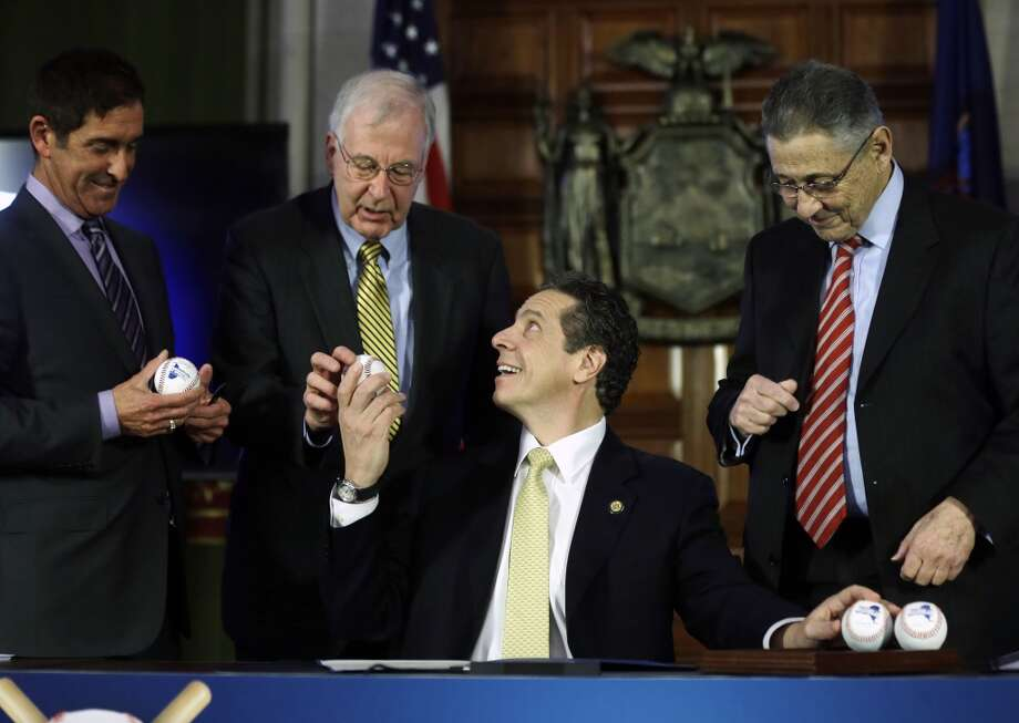 New York Gov. Andrew Cuomo, seated, hands out baseballs to Senate co-leader Jeff Klein, D-Bronx, from left, Sen. Kemp Hannon, R-Garden City, and Assembly Speaker Sheldon Silver, D-Manhattan, during a news conference and budget bill signing ceremony in the Red Room at the Capitol on Tuesday, April 1, 2014, in Albany, N.Y. The baseballs represent a grand slam budget after four consecutive on-time budgets. (AP Photo/Mike Groll) Photo: Mike Groll, AP