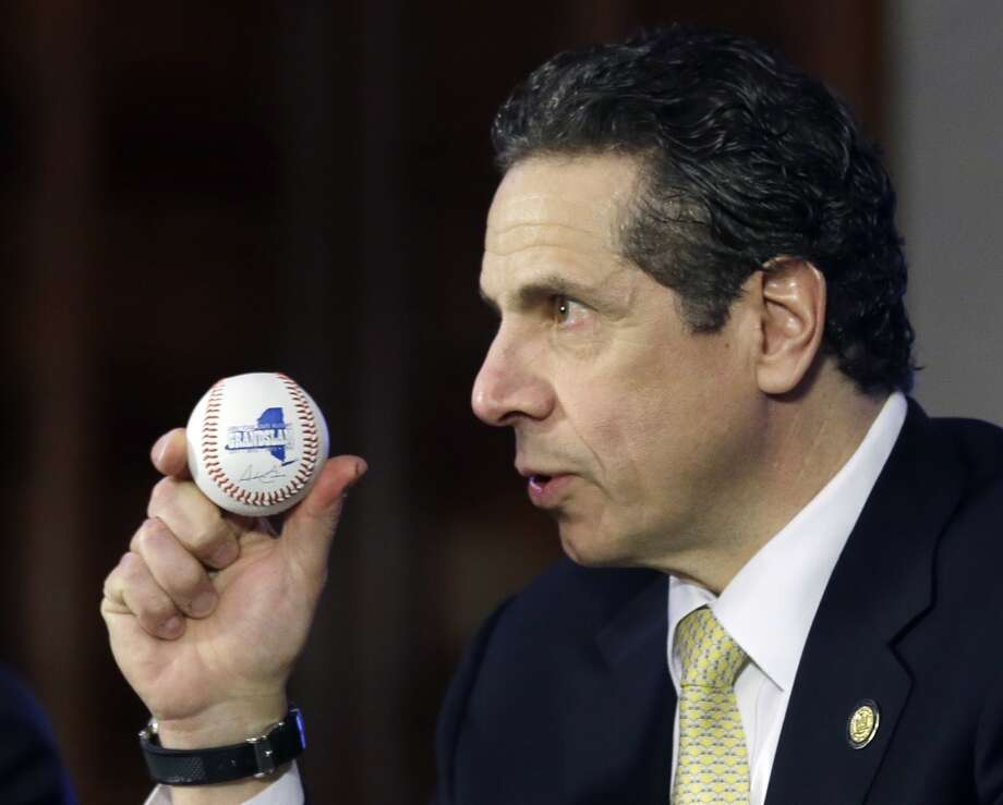 New York Gov. Andrew Cuomo holds a baseball as he speaks during a news conference and budget bill signing ceremony in the Red Room at the Capitol on Tuesday, April 1, 2014, in Albany, N.Y. The New York Legislature on Monday passed a $140 billion election-year budget that will expand pre-kindergarten statewide and provide tax relief to homeowners and corporations. (AP Photo/Mike Groll) Photo: Mike Groll, AP