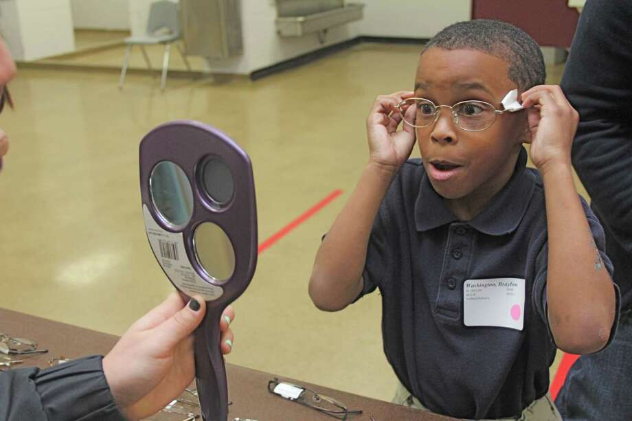 Braylon Washington, 7, first-grader at Stafford Primary School, reacts when he sees himself in a mirror while selecting frames for new glasses at Wheeler Field House at the See to Succeed program. Braylon Washington, 7, first-grader at Stafford Primary School, reacts when he sees himself in a mirror while selecting frames for new glasses at Wheeler Field House at the See to Succeed program. Photo: Suzanne Rehak, Freelance Photographer