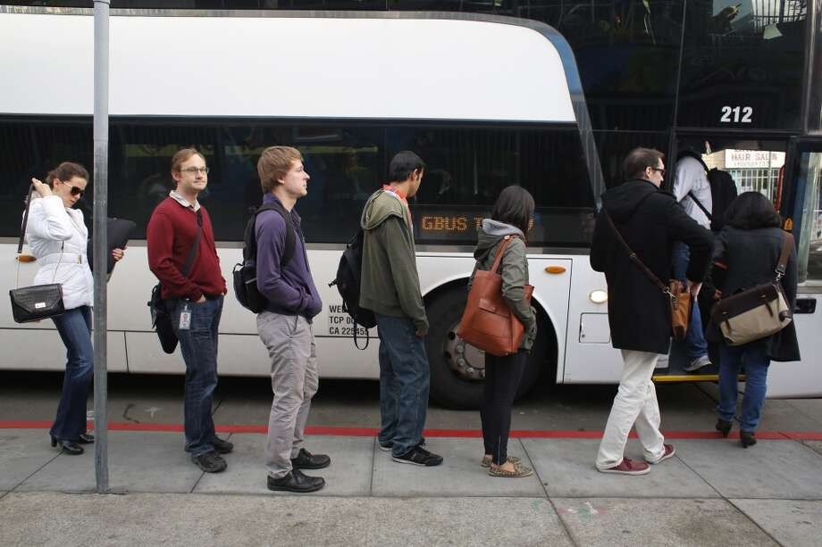 A group of Google employees load up on a Google bus at 24th Street at Valencia Street. Photo: Mike Kepka, The Chronicle