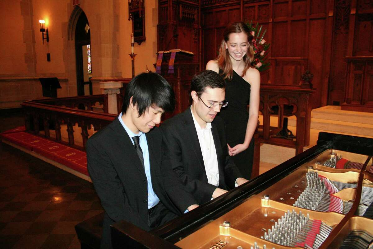 Kenneth Yu and Kerrigan Quenemoen watch as Dr. Matthew Loudermilk explains how to play a difficult passage in the music. Quenemoen and Yu will be competing for national honors in the High School Piano Duet category at the Music Teachers National Association in Chicago.